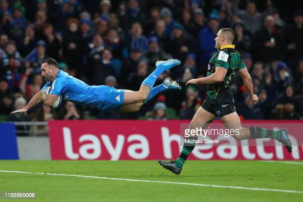 Dave Kearney of Leinser dives over to score his third try as Ollie Sleightholme of Northampton Saints looks on during the Heineken Champions Cup...