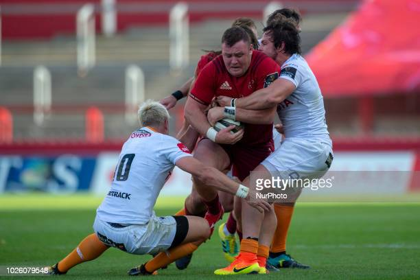 Dave Kilcoyne of Munster tackled by Nico Lee and Tian Schoeman of Cheetahs during the Guinness PRO14 rugby match between Munster Rugby and Toyota...