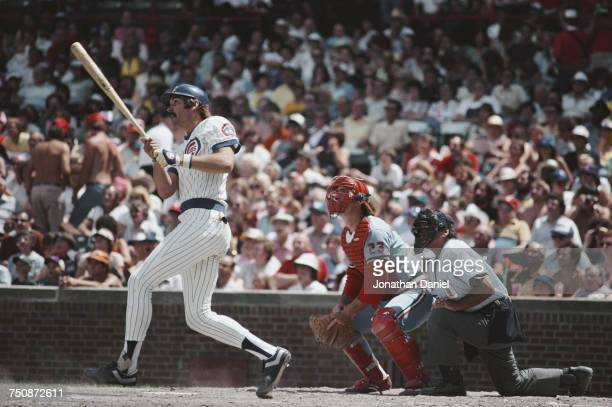 Dave Kingman in fielder for the Chicago Cubs swings his bat at the plate as Ted Simmons catcher for the Cardinals and home plate umpire Dutch Rennert...