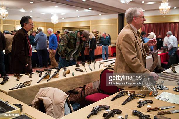 Dave Kleiner of Gettysburg Pennsylvania sells antique guns at a gun show at the Crowne Plaza Hotel on January 5 2013 in Stamford Connecticut While...