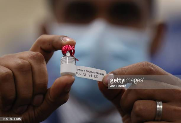 Dave Lacknauth, Executive Director of Pharmacy Services, Broward Health Medical Center, shows off a bottle containing the Pfizer-BioNtech COVID-19...