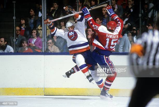 Dave Langevin of the New York Islanders and Alan Haworth of the Washington Captials collide during their game circa 1985 at the Nassau Coliseum in...