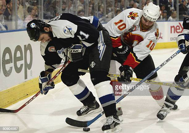 Dave Lowry of the Calgary Flames and Cory Sarich of the Tampa Bay Lightning battle for the puck in game two of the NHL Stanley Cup Finals on May 27...