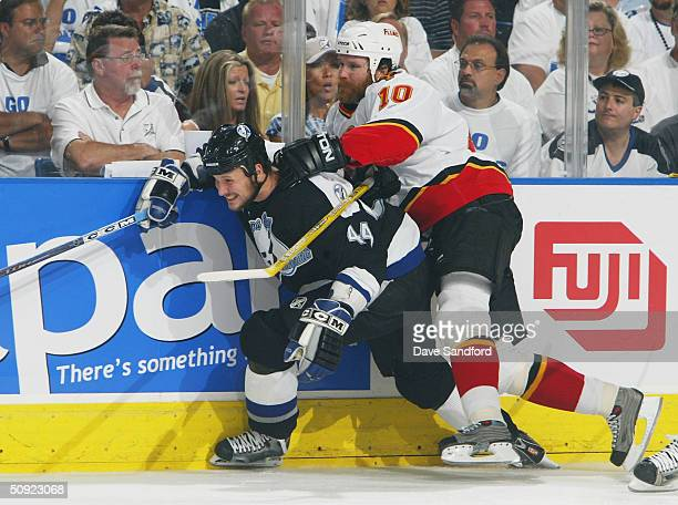 Dave Lowry of the Calgary Flames battles Nolan Pratt of the Tampa Bay Lightning against the boards during the first period in game five of the NHL...