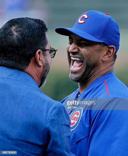 Dave Martinez of the Chicago Cubs laughs while talking with former Chicago White Sox manager Ozzie Guillen before the game between the Chicago White...