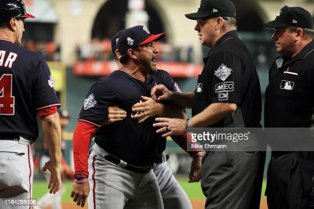 Dave Martinez of the Washington Nationals argues as he is ejected by the umpire and is held back by Chip Hale against the Houston Astros after the...