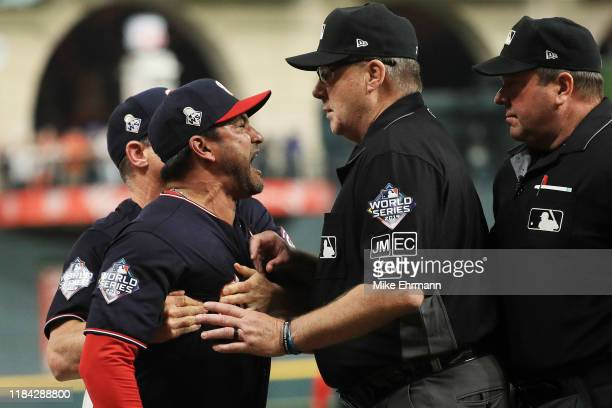 Dave Martinez of the Washington Nationals argues with umpire Gary Cederstrom as he is ejected and is held back by Chip Hale against the Houston...