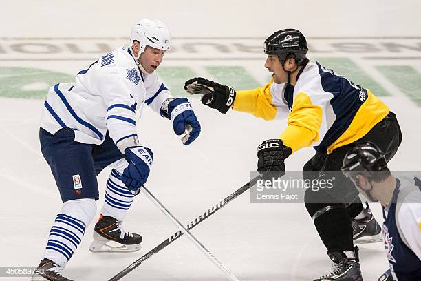 Dave McLlwain of the Toronto Maple Leafs Alumni battles against Bob Boughner of the Windsor Spitfires Alumni on November 8 2013 at the WFCU Centre in...