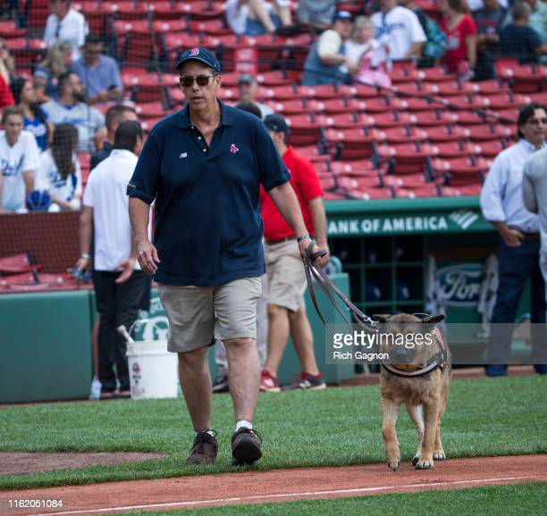 Dave Mellor the groundskeeper of the Boston Red Sox walks with his dog Drago before a game against the Los Angeles Dodgers at Fenway Park on August...