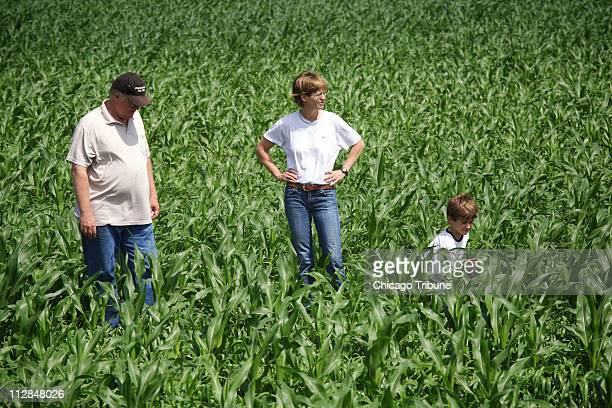 Dave Miller, of Winnetka, left, points out different types of weeds in a field of organic corn with DD Burlin, of River Forest, center, and her son,...