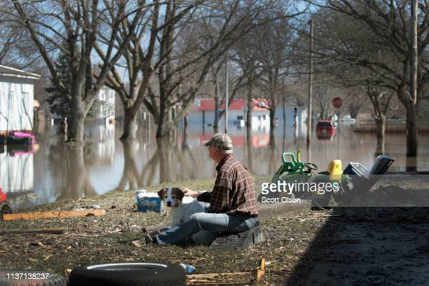 Dave Mincer sits along a flooded street with a friend's dog on March 20 2019 in Hamburg Iowa Although flood water in the town has started to recede...