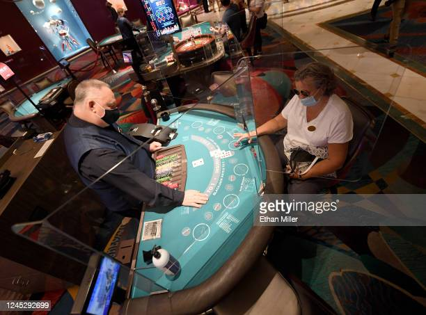 Dave Mitchell deals cards to Tammy Spears of Nevada at a blackjack table with plexiglass safety shield dividers at Bellagio Resort & Casino on the...