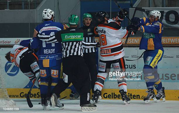 Dave Reid of Muenchen fights with Ken Magowan of Wolfsburg and his team mate Sebastian Furchner during the DEL match between EHC Muenchen and Grizzly...