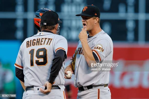 Dave Righetti of the San Francisco Giants talks to Matt Cain on the pitchers mound against the Oakland Athletics during the first inning at the...