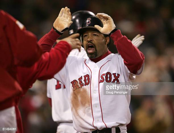 Dave Roberts of the Boston Red Sox celebrates with his teammates after scoring on a game tying sacrafice fly-out by teammate Jason Varitek in the...