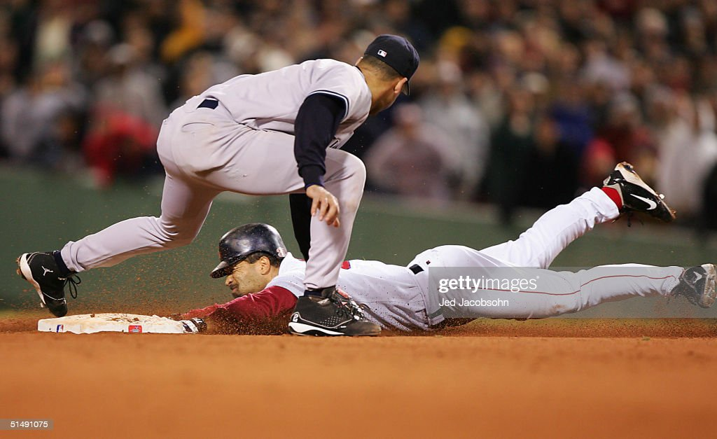 Dave Roberts #31 of the Boston Red Sox steals second base while shortstop Derek Jeter #2 of the New York Yankees applies the tag in the ninth inning during game four of the American League Championship Series on October 17, 2004 at Fenway Park in Boston, Massachusetts.