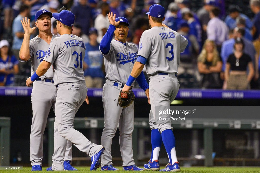 Dave Roberts #30 of the Los Angeles Dodgers congratulates Joc Pederson #31 and Chris Taylor #3 after an 8-5 win over the Colorado Rockies at Coors Field on August 9, 2018 in Denver, Colorado.