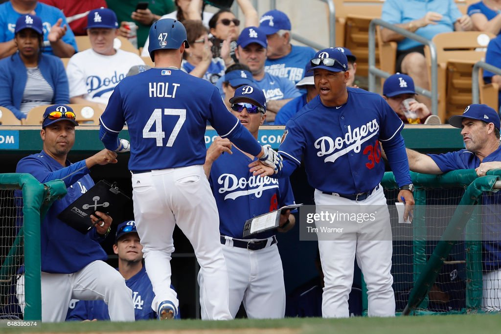 Dave Roberts #30 of the Los Angeles Dodgers congratulates Tyler Holt #47 after scoring in the seventh inning against the Seattle Mariners during the spring training game at Camelback Ranch on March 5, 2017 in Glendale, Arizona.