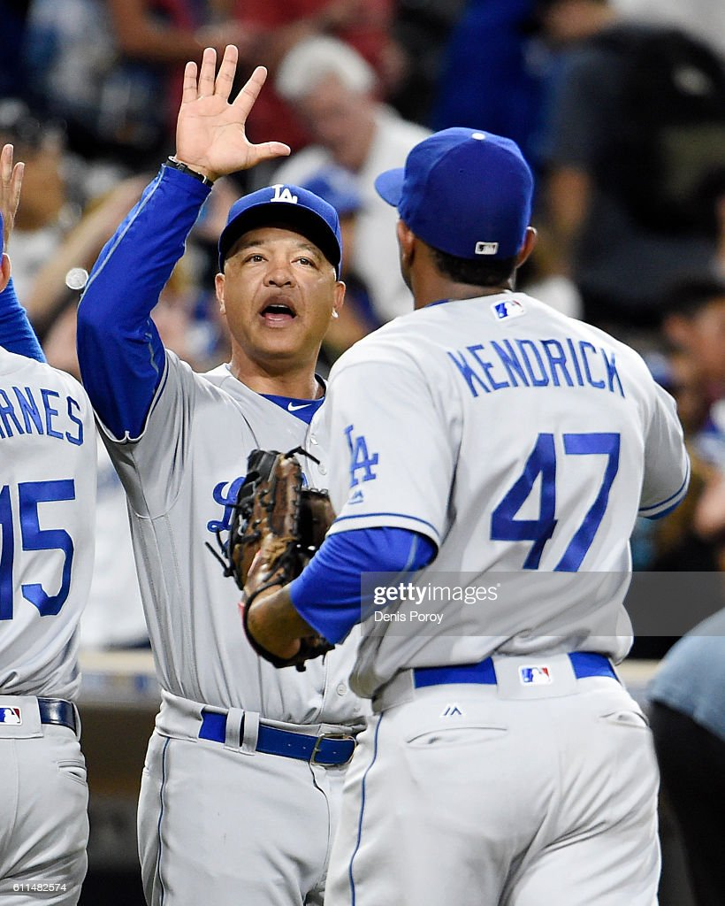 Dave Roberts #30 of the Los Angeles Dodgers, left, congratulates Howie Kendrick #47 after beating the San Diego Padres 9-4 in a baseball game at PETCO Park on September 29, 2016 in San Diego, California.