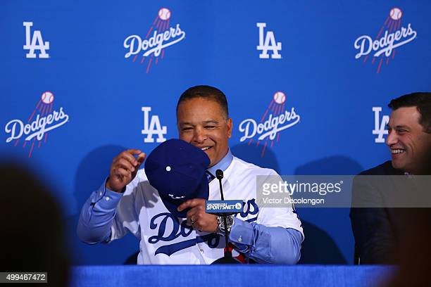 Dave Roberts puts on a Dodgers hat as Andrew Friedman right Dodgers President of Baseball Operations looks on during a press conference to introduce...