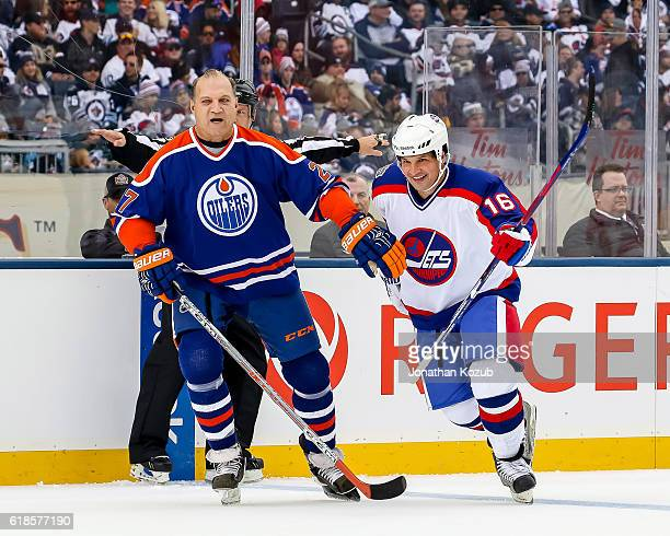 Dave Semenko of the Edmonton Oilers alumni holds back Eddie Olczyk of the Winnipeg Jets alumni during first period action in the 2016 Tim Hortons...