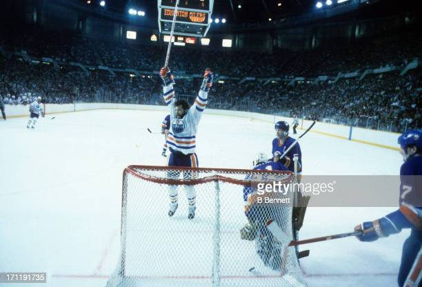 Dave Semenko of the Edmonton Oilers celebrates his goal as goalie Billy Smith and Denis Potvin of the New York Islanders look dejected during the...