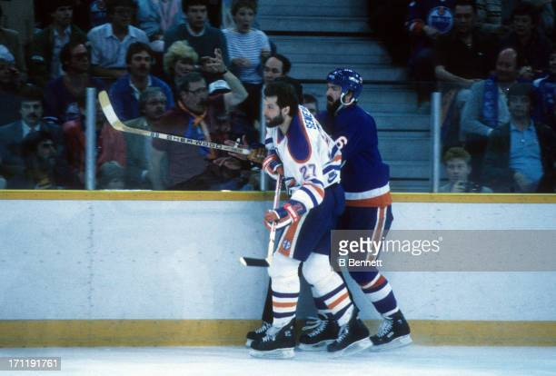 Dave Semenko of the Edmonton Oilers checks Ken Morrow of the New York Islanders during the 1984 Stanley Cup Finals in May 1984 at the Northlands...