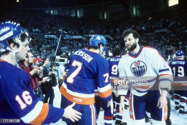 Dave Semenko of the Edmonton Oilers shakes hands with Pat LaFontaine and Stefan Persson of the New York Islanders after Game 5 of the 1984 Stanley...