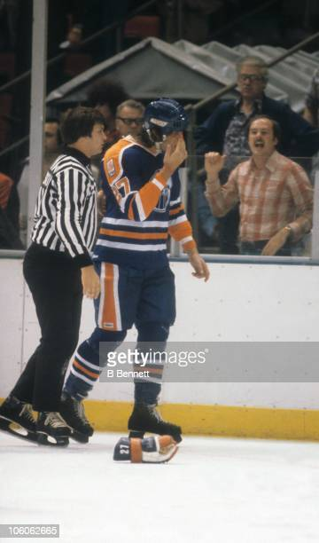 Dave Semenko of the Edmonton Oilers wipes blood off his face after a fight during an NHL game against the New York Islanders on October 23 1979 at...