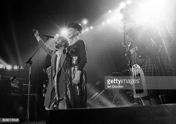 Dave Stewart and Annie Lennox of Eurythmics performing on stage with bagpipe players at Touch Tour Lyceum Theatre London 30 November 1983