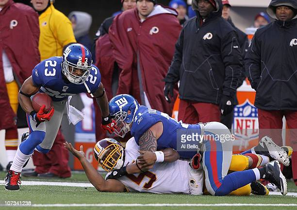 Dave Tollefson of the New York Giants sacks Donovan McNabb of the Washington Redskins who fumbles and the ball is recovered by Corey Webster during...
