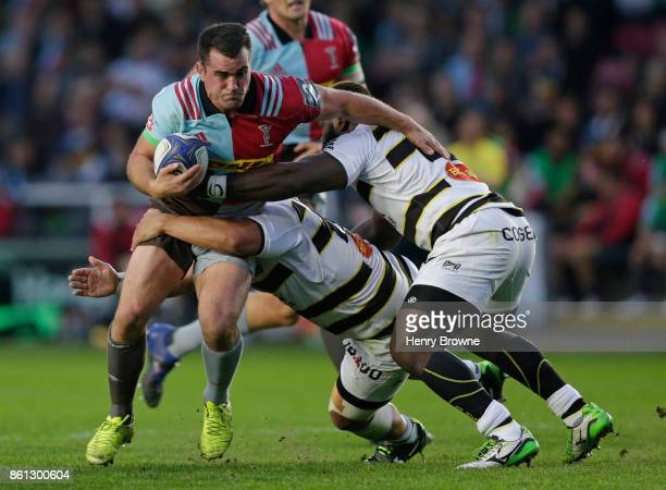 Dave Ward of Harlequins tackled by Hikairo Forbes and Dany Priso of La Rochelle during the European Rugby Champions Cup match between Harlequins and...