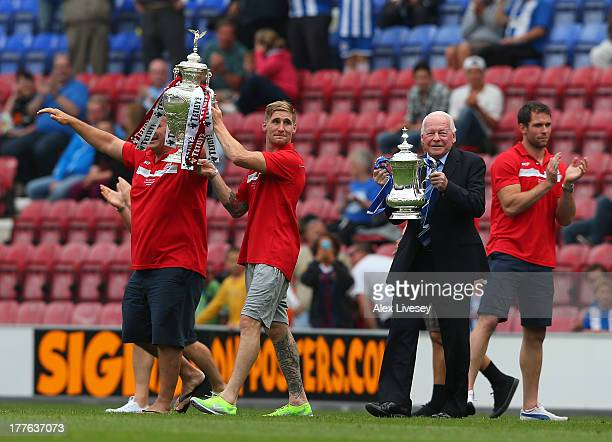 Dave Whelan the chairman of Wigan Athletic and Sam Tomkins of Wigan Warriors show off the Rugby League Challenge Cup and the FA Cup to the crowd...
