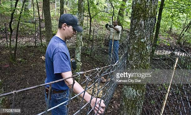 Dave Woods left with the Missouri Department of Conservation and James Dixon a state wildlife damage biologist reset a wild hog trap May 17 in Taney...