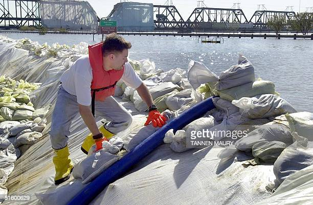 Davenport city employee checks on one of the pump hoses discharging floodwater back into the Mississippi River 24 April 2001 in Davenport Iowa...