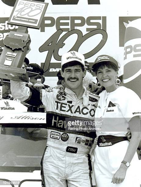 Davey Allison celebrates in Victory Lane after winning the Pepsi 400 Allison would win $65000 for the race