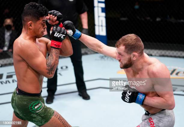 Davey Grant of England punches Jonathan Martinez in a bantamweight fight during the UFC Fight Night event at UFC APEX on March 13, 2021 in Las Vegas,...