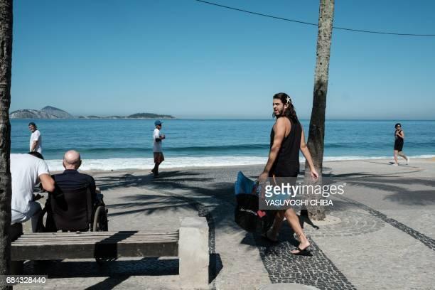 Davi de Oliveira Moreira known as Sereio carries his mermaid tail costume as he walks along Ipanema Beach in Rio de Janeiro Brazil on May 3 2017 The...