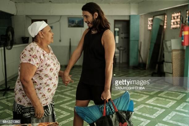 Davi de Oliveira Moreira known as Sereio greets his 69yearold neighbor Joana Darc who runs a restaurant before heading out to the beach in Rio de...