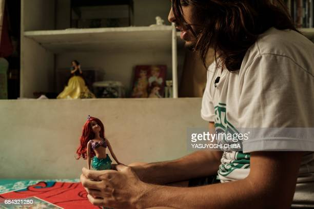 Davi de Oliveira Moreira known as Sereio holds a doll of Disney's mermaid caracter Ariel at his home in Rio de Janeiro Brazil on May 3 2017 The...