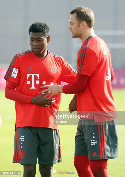 David Alaba and goalkeeper Manuel Neuer of FC Bayern Muenchen chat during a training session at the club's Saebener Strasse training ground on...