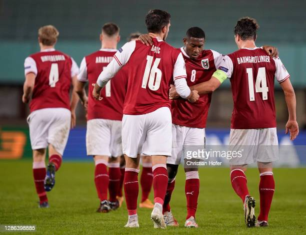 David Alaba embraces team mates Adrian Grbic and Julian Baumgartlinger of Austria following the UEFA Nations League group stage match between Austria...