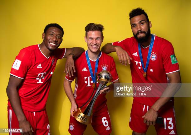 David Alaba, Joshua Kimmich and Eric Maxim Choupo-Moting of FC Bayern Muenchen poses with the trophy after winning the FIFA Club World Cup Qatar 2020...