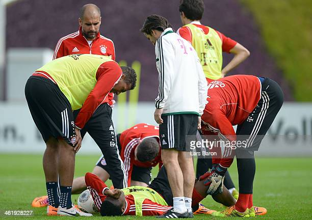 David Alaba lies injured on the pitch next to head coach Josep Guardiola during a training session at day 8 of the Bayern Muenchen training camp at...