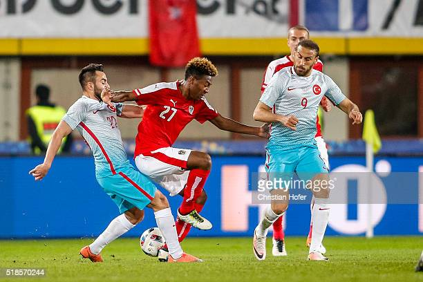 David Alaba of Austria competes for the ball with Volkan Sen and Cenk Tosun of Turkey during the international friendly match between Austria and...