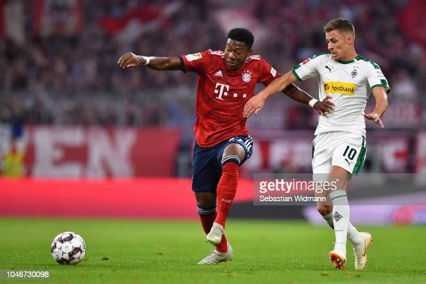 David Alaba of Bayern Muenchen and Thorgan Hazard of Moenchengladbach compete for the ball during the Bundesliga match between FC Bayern Muenchen and...