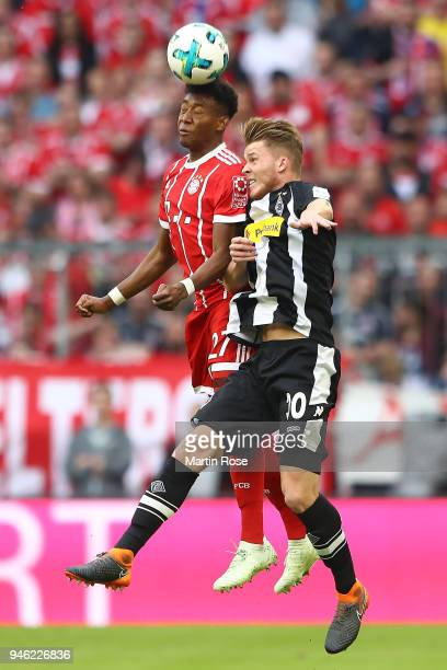 David Alaba of Bayern Muenchen fights for the ball with Nico Elvedi of Moenchengladbach during the Bundesliga match between FC Bayern Muenchen and...