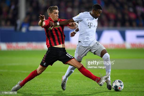 David Alaba of Bayern Munich battles for the ball with Nils Petersen of SC Freiburg during the Bundesliga match between Sport-Club Freiburg and FC...