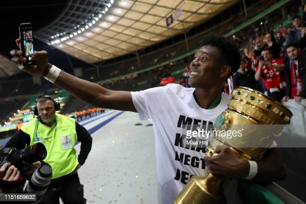 David Alaba of Bayern Munich celebrates with the DFB Pokal following his team's victory in the DFB Cup final between RB Leipzig and Bayern Muenchen...