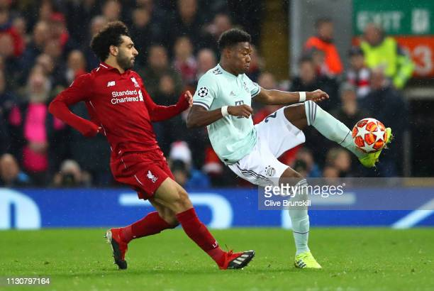David Alaba of Bayern Munich clears from Mohamed Salah of Liverpool during the UEFA Champions League Round of 16 First Leg match between Liverpool...
